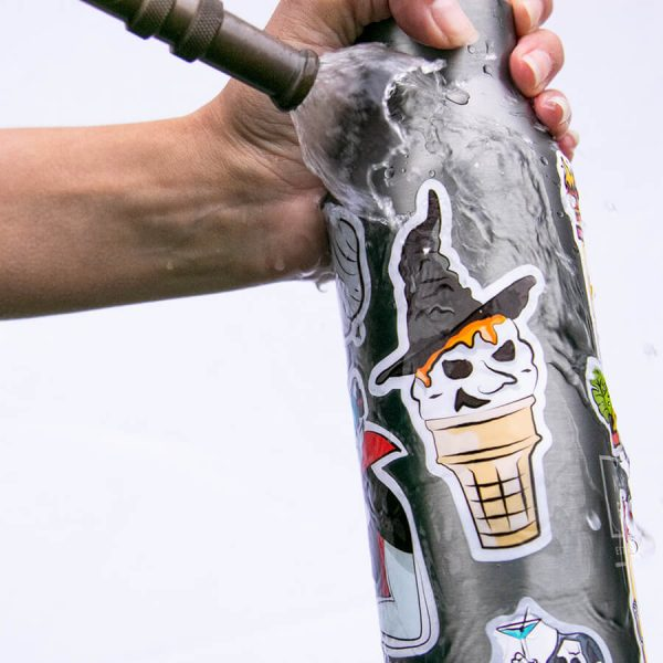 Stickers stuck on water bottle with hose water running over it (Showing that it's weatherproof) | Ash Robertson Design Stickers